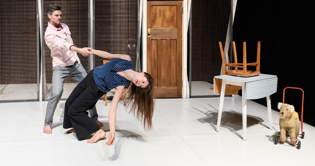 Man en vrouw dansen in huis. Ze hebben elkaar met 1 hand en gestrekte arm vast. De vrouw hangt met een holle rug helemaal achterover.