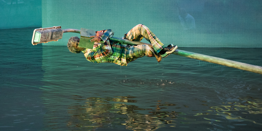scenefoto Vis a Vis: een lantaarnpaal hangt bijna horizontaal boven water, een natte man hangt er in en leest een boek