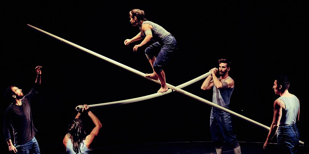 Tipping Point acrobate balanceert op lange stokken, kruislings vastgehouden door anderen